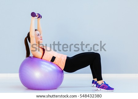 Beautiful  fitness woman training with dumbbells on fitness ball