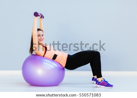 Beautiful  fitness woman training with dumbbells on fitness ball.