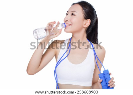 beautiful fitness woman with bottle of water and skipping rope. sport. white background. - stock photo