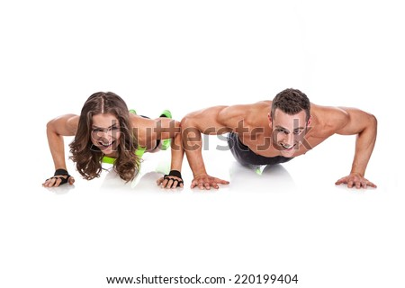 beautiful fitness young sporty couple doing push ups isolated over white background - stock photo