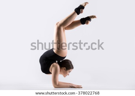 Beautiful flexible young gymnast athlete woman in black leotard working out, doing acrobatic exercise, handstand with backbend, full length, studio, white background, isolated - stock photo