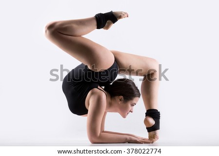 Beautiful flexible young gymnast athlete woman in black leotard working out, doing art gymnastics handstand, acrobatic exercise, full length, studio, white background, isolated - stock photo
