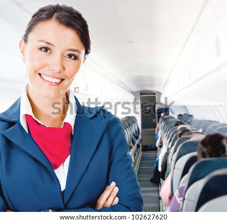 Beautiful flight attendant in an airplane smiling - stock photo