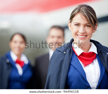 Beautiful flight attendant with the cabin crew at the background - stock photo