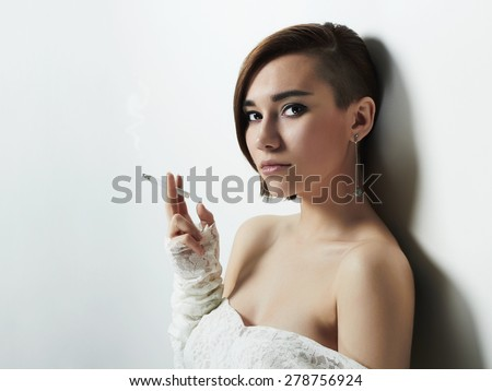 beautiful flirt young woman with short haircut smoking cigarette.beauty girl in wedding dress - stock photo