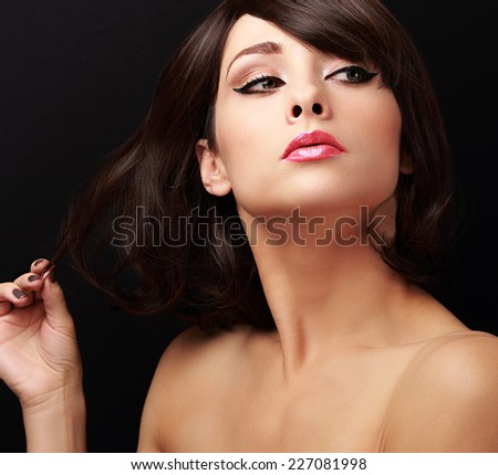 Beautiful flirting woman looking calm. Closeup portrait on black background - stock photo