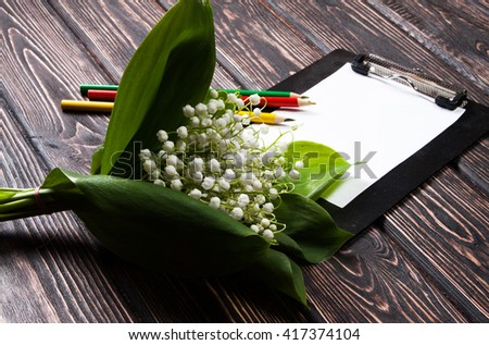 Beautiful floral frame with lilies of the valley flowers and clipboard on old wooden table. - stock photo