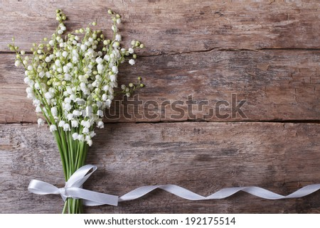 Beautiful floral frame with lilies of the valley flowers on old wooden table. horizontal  - stock photo