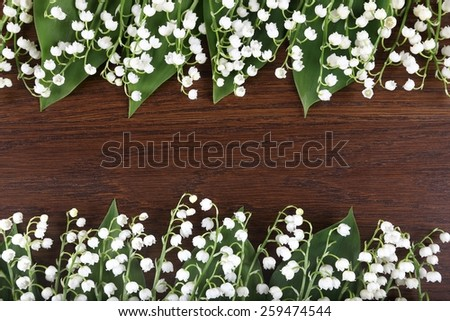 Beautiful floral frame with lilies of the valley flowers on wooden background. - stock photo