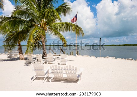 Beautiful Florida Keys along the shoreline with lounge chairs and gulf view.