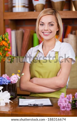 Beautiful florist at work. Beautiful young female florist keeping arms crossed and smiling at camera while standing at her working place full of flowers - stock photo