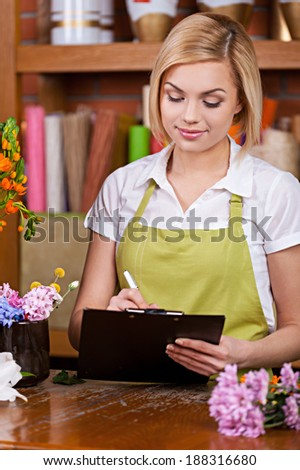 Beautiful florist at work. Beautiful young female florist writing something at note pad and taking on the phone while standing at her working place - stock photo