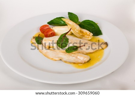 beautiful flow of white fish fillet with beetroot leaves and yellow sauce on a white background isolated for menus - stock photo