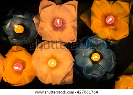 Beautiful flower garlands and colored lanterns are released for celebrating Buddha's birthday in Saigon River by night, a Eastern culture. - stock photo