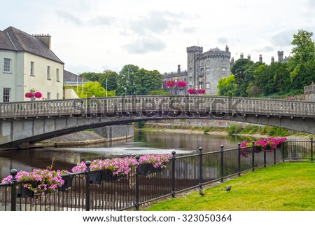 beautiful flower lined riverside railings view of kilkenny castle town and bridge - stock photo