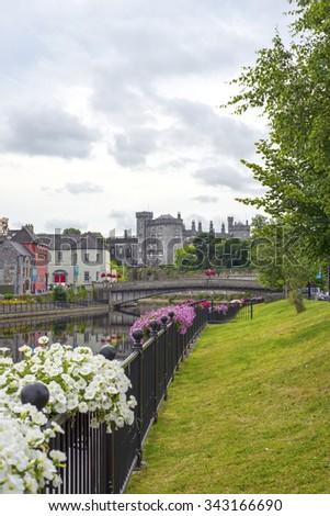beautiful flower lined riverside view of killkenny castle and bridge - stock photo