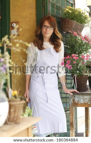 Beautiful flower shop owner standing at facade. - stock photo