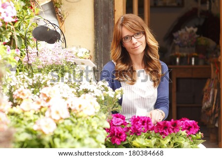 Beautiful flower shop owner standing in her store. - stock photo