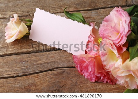Beautiful flowers and gift card on wooden background