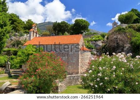 Beautiful flowers around Orthodox monastery church in Mediterranean area, Montenegro - stock photo