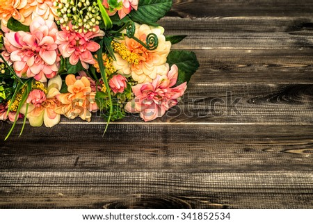 Beautiful flowers bouquet on wood background useful as greeting card.