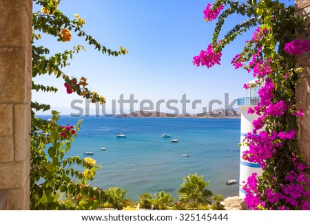 Beautiful flowers can be seen past the Lighthouse at Ortakent in Turkey with blue/green seas stretching to the horizon. - stock photo