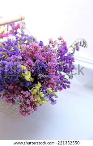 Beautiful flowers in basket on window background - stock photo