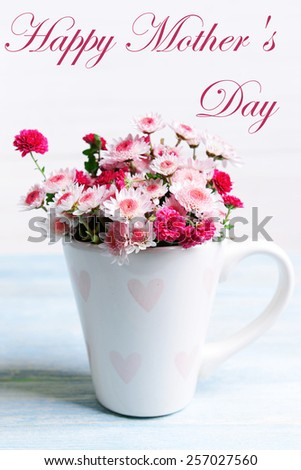Beautiful flowers in cup on table on light background, Mother's Day concept - stock photo