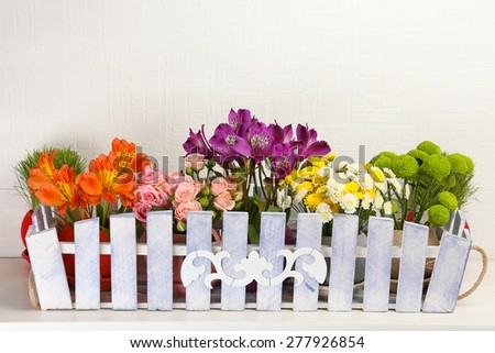 Beautiful flowers in ornamental flowerpot on light background - stock photo