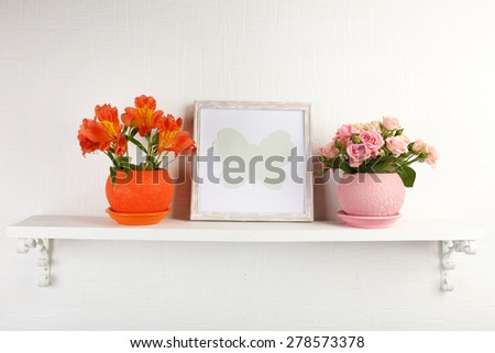 Beautiful flowers in pots on shelf on wall background - stock photo
