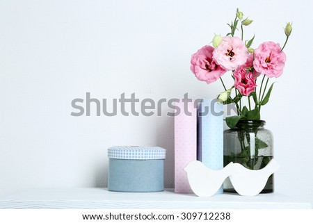 Beautiful flowers in vase with books on wall background - stock photo
