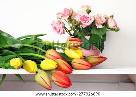 Beautiful flowers on shelf on wall background - stock photo