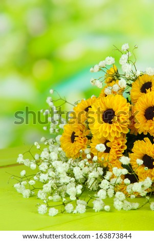 Beautiful flowers on table on bright background