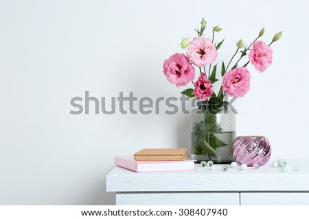 Beautiful flowers with books on wall background - stock photo