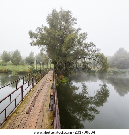 beautiful foggy morning in the russia, wooden bridge and tree - stock photo