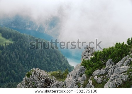 Beautiful foggy view on the Koenigssee and forest  from Jenner mountain, a peak in Berchtesgaden, Germany - stock photo