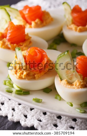 Beautiful food: Eggs stuffed with salmon and cucumber closeup on a plate. vertical