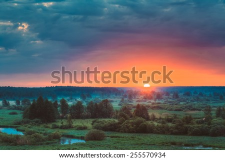 Beautiful Forest On Sunrise. Dramatic Sky With Sunset Sun Over Morning Meadow - stock photo