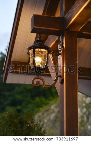 Beautiful forged lantern under the wooden roof