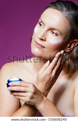beautiful forty year old woman with natural makeup and healthy skin texture on pink studio background. Applying facial cream from a cosmetics tub - stock photo