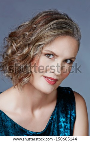 Beautiful fourty year old woman with fashion makeup, curly hairstyle on grey blue studio background. Wearing green velvet dress - stock photo