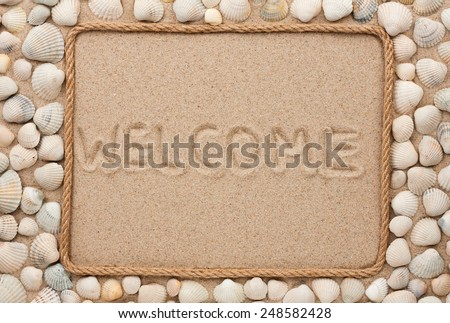 Beautiful frame of rope and sea shells on the sand with text welcome, as background - stock photo