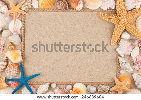 Beautiful frame of rope and seashells on the sand, with place for your image, text - stock photo