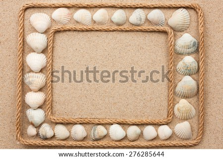 Beautiful frame with rope and sea shells on sand, as a background
