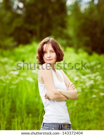Beautiful freckled young woman with folded arms standing in summer field