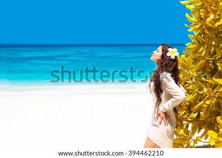 Beautiful free woman enjoying on exotic beach in summer by tropical blue water. Attractive girl with long hair sunbathing and resting, outdoor portrait. Bliss freedom concept. Travel. - stock photo