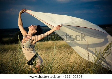 Beautiful free woman in white underwear playing with transparent scarf in summer field opposite to blue moody sky - stock photo