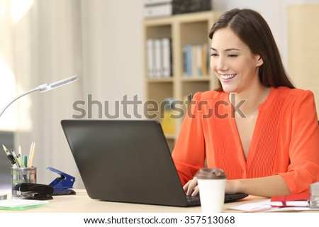 Beautiful freelancer working with a laptop in a desk at home room or office - stock photo