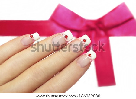 Beautiful French manicure with pink and red hearts on the nails. - stock photo
