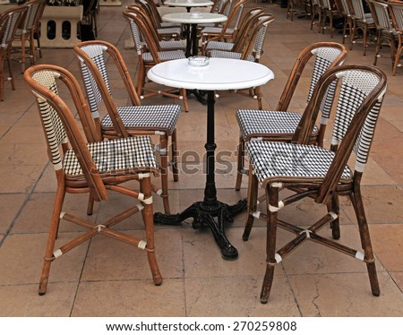 Beautiful french outdoor cafe with small round tables and wicker chairs, Cote d'Azur, France - stock photo